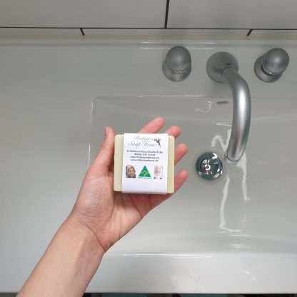 hand over bathroom sink holding small square solid shampoo bar australian made hand made plastic free paper compostable packaging